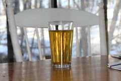 Craft beer in pint glass. Home brewed beer on wood table. White chair and view out window of trees and snow in the background Royalty Free Stock Photos