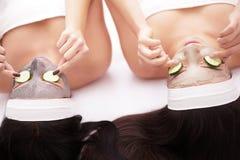 home brunnsort Två härliga unga kvinnor som rymmer stycken av gurkan på deras ögon och ler medan på sängen Royaltyfri Fotografi