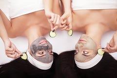 home brunnsort Två kvinnor som rymmer stycken av gurkan på deras framsidor som ligger sängen Arkivfoto