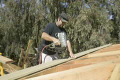 A home builder shooting nails into the roof Royalty Free Stock Image