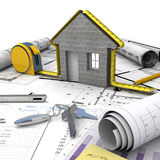 Home building process. A house under construction on top of a table with mortgage application form, calculator, blueprints, etc royalty free stock photo