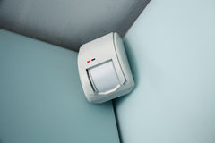 Home burglar alarm sensor. Burglar alarm movement sensor mounted on a wall stock photo