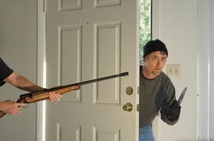 Home burglary thief being caught at gunpoint Stock Photos