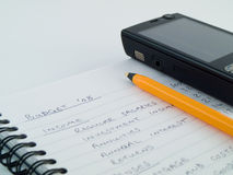 Home Business Budget With Mobile Phone. On Ringbound Lined White Note paper stock photography