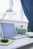 Home and Business office interior set up. With a mobile phone and laptop on a white desk royalty free stock photography