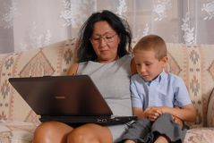 Home Business Woman 15. Business woman at home with son working on computer royalty free stock photography