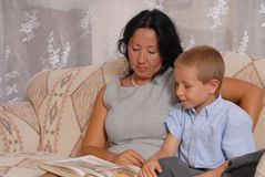Home Business Woman 18. Business woman at home with son reading royalty free stock photo