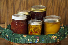 Home Canned Fruits and Vegetables. Basket of home canned peaches, corn relish, strawberry rhubarb preserves, and cherry jelly on a wooden shelf. Gifts from the Royalty Free Stock Photo