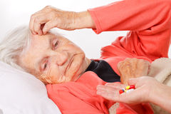 Home care. Caregiver giving medication to her senior patient Stock Photo