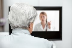 In-home care for an elderly patient with telemedicine or telehealth, virtual live chat. On the monitor royalty free stock images