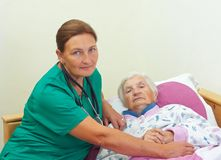 Home care. Elderly women with her caregiver at home stock photography
