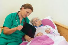 Home care. Elderly women with her caregiver at home royalty free stock image