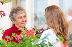 Home care. Happy elderly women and her helpful assistant royalty free stock photo