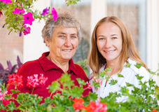 Home care. Happy elderly women and her helpful assistant stock images