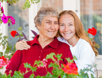 Home care. Happy elderly women and her helpful assistant royalty free stock images