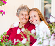 Home care. Happy elderly women and her helpful assistant stock image