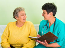 Home care. Photo of happy elderly women with the doctor royalty free stock photo