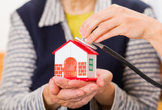 Home care. Photo of a miniature house holding in hands stock photography