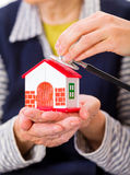 Home care. Photo of a miniature house holding in hands royalty free stock image