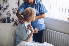 Home caregiver dressing senior stock photos