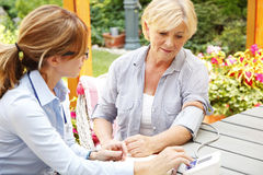 Home caregiver. Portrait of home caregiver measuring the blood pressure. Middle age health care working consulting with senior women while sitting at nursing stock image