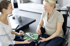 Home carer with elderly woman playing social game Royalty Free Stock Image