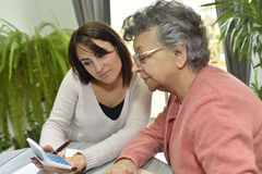 Home carer helping the elderly with paperwork. Home helper taking care of elderly woman's paperwork Stock Photo