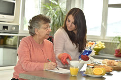 Home carer helčping a senior woman doing crossword Royalty Free Stock Images