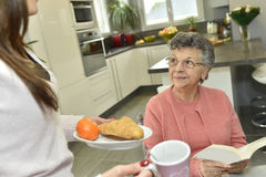 Home carer serving food to an elderly woman. Home helper serving breakfast to elderly woman Royalty Free Stock Photography