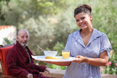 Home carer serving meal to elderly man Royalty Free Stock Image