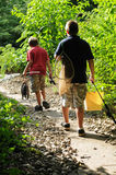 Home with the catch. Two brothers (10, 13) on a path through the woods, after a day's fishing Royalty Free Stock Image