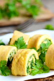 Home cheese and parsley stuffed omelet rolls on a plate. Cut fried omelet with grated cheese and finely chopped parsley. Tasty and gluten free breakfast omelet stock image