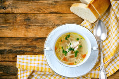 Home chicken soup with noodles, vintage spoon, tablecloth Royalty Free Stock Images