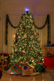 Home Christmas. Christmas Tree in warm home, lights on,presents under tree Stock Photography