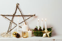 Home Christmas decoration. Christmas decoration with golden ornaments, candles, lights and a star made of natural sticks Stock Photo