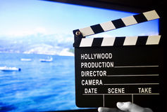 Home cinema. Concept: directors cut clapboard plate in front of a big hdtv plasma screen royalty free stock photos