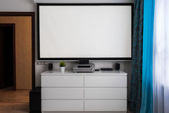 Home cinema center in livingroom. Home multimedia center  with wide cinema theater screen in room. Space for text on screen Stock Image