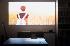 Home cinema: watching a film from a video projector in a room. Dim living room with a cinematic picture projected on the wall royalty free stock images