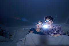 Home cinema. Young couple enjoying home cinema in dark room royalty free stock photo