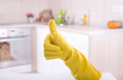 Home cleaning concept. Conceptual image of home cleaning. Close up of human hand with yellow rubber glove showing ok sign with thumb up. Cleaned kitchen in royalty free stock photos
