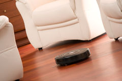 Home cleaning robot. Home vacuum cleaning robot in action on genuine living room wooden floor. Selective focus on robot stock photo