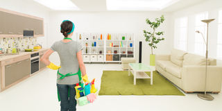 Home cleaning. Young caucasian woman standing in clean house holding cleaning products, looking at tidy room stock photography