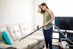 Home and cleanliness - Woman cleaning sofa. Attractive tired woman hoovering sofa in using vacuum cleaner Stock Image