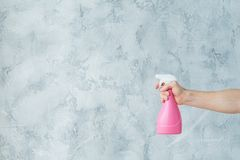 Home cleanup window cleaning hand hold atomizer. Home cleanup strategy. Window cleaning. Hand holding atomizer. Copy space on grey textured background royalty free stock image