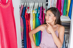Home closet clothing rack girl thinking of outfit. Home closet or store clothing rack changing room. Woman choosing her fashion outfit. Shopping girl thinking stock images