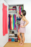 Home closet - woman choosing her fashion clothing. Shopping concept. Woman having many new clothes facing indecision in front of many choices of stylish Stock Photography
