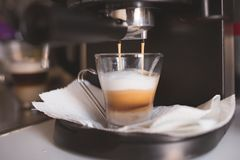 Home coffee preparation with an expresso machine. Coffee prepared with a household expresso machine. Capuccino in the making, reach foam stock image
