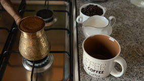 The home coffee in stove. Coffee is already cooked on the stove. He is poured into a mug. In the background, there is a cup of coffee in the jar and milk. All stock video footage