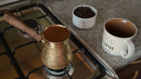 The home coffee in stove. Coffee beans are cooked on the stove. In the background in the frame there is a mug and coffee beans in a jar. All this is on the stock video footage