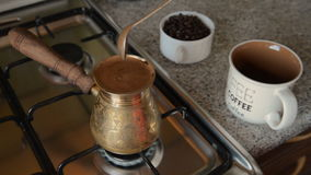 The home coffee in stove. Coffee beans are cooked on the stove. In the background in the frame there is a mug and coffee beans in a jar. All this is on the stock footage